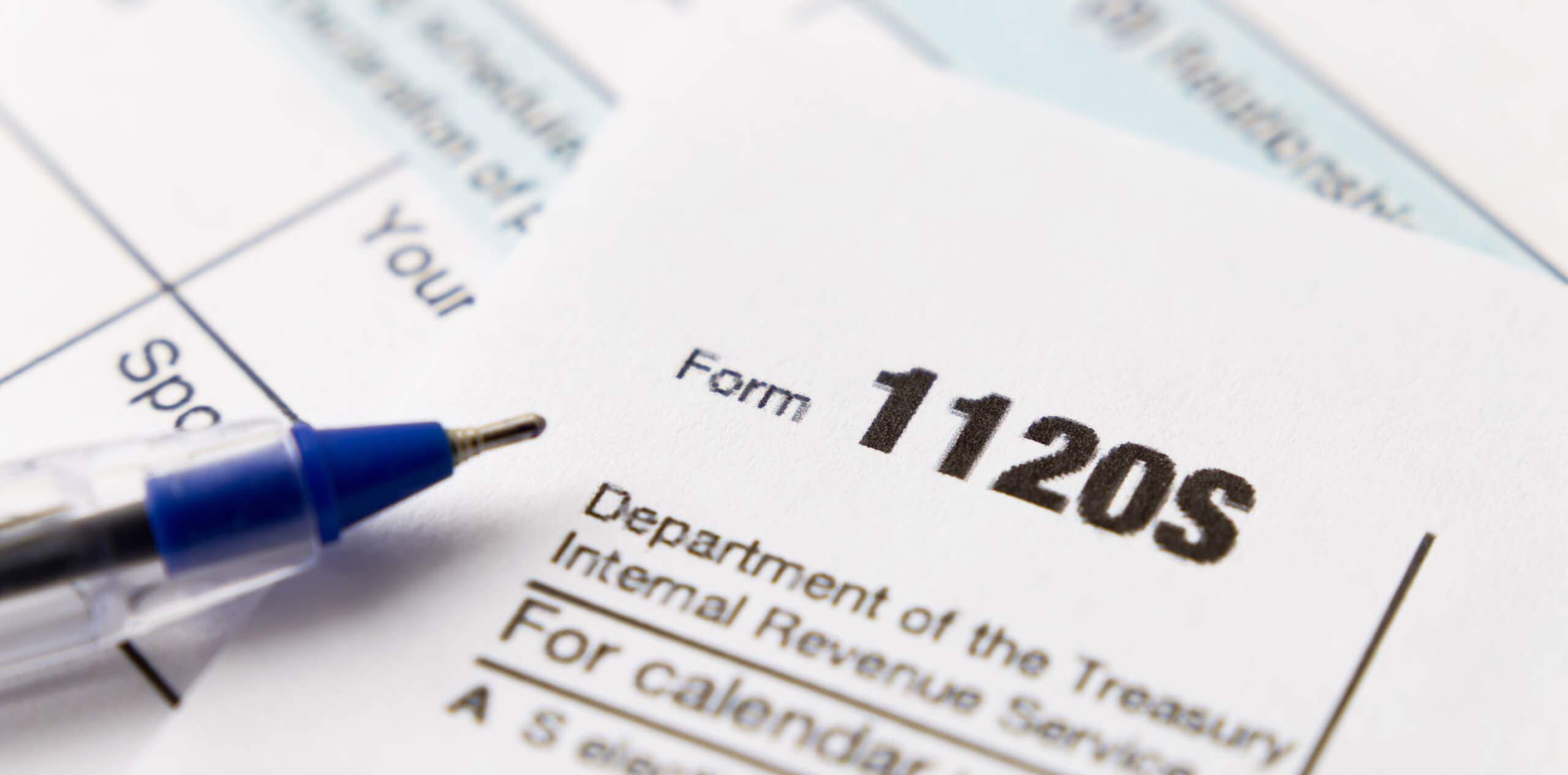Tax forms on a table with a pen laying on top
